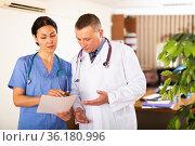 Two doctors discussing medical card of patient in office. Стоковое фото, фотограф Яков Филимонов / Фотобанк Лори