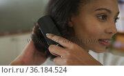 Portrait of mixed race woman wearing bathrobe brushing her hair. Стоковое видео, агентство Wavebreak Media / Фотобанк Лори