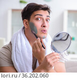 Handsome applying clay mask on face. Стоковое фото, фотограф Elnur / Фотобанк Лори