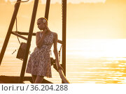 Girl in a dress with a short haircut stands on a rustic water intake against the backdrop of a river in the sun. Стоковое фото, фотограф Евгений Харитонов / Фотобанк Лори