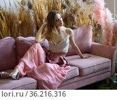 Nice woman sitting on a sofa in a room in tall grass. Стоковое фото, фотограф Алексей Кузнецов / Фотобанк Лори