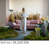 Pleasant young woman in a room with sofa in the middle of tall grass. Стоковое фото, фотограф Алексей Кузнецов / Фотобанк Лори