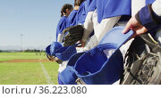 Midsection of team of female baseball players standing in line on field holding helmets and gloves. Стоковое видео, агентство Wavebreak Media / Фотобанк Лори