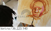 African american male artist wearing face mask painting on canvas at art studio. Стоковое видео, агентство Wavebreak Media / Фотобанк Лори