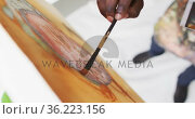 Overhead view of male artist painting on canvas looking at photo at art studio. Стоковое видео, агентство Wavebreak Media / Фотобанк Лори