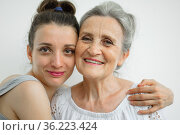 Happy senior mother is hugging her adult daughter, the women are laughing together, sincere family of different age generations having fun on white background, mothers day. Стоковое фото, фотограф Ольга Балынская / Фотобанк Лори