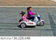6 bis 8jährige Mädchen fährt mit ihrer Schwester auf einem elektrisch... Стоковое фото, фотограф Zoonar.com/Georg / age Fotostock / Фотобанк Лори
