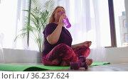 Fitness training - blonde overweight woman sitting on yoga mat and drinks water from a bottle. Стоковое видео, видеограф Константин Шишкин / Фотобанк Лори