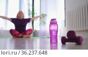 Fitness training - overweight woman meditating on yoga mat - a bottle of water and little dumbbells on the foreground. Стоковое видео, видеограф Константин Шишкин / Фотобанк Лори