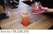 Barista puts pieces of dried orange on top of a beverage. Стоковое видео, видеограф Константин Шишкин / Фотобанк Лори