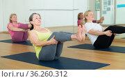 People relaxing and enjoying yoga elements - boat pose. Стоковое фото, фотограф Яков Филимонов / Фотобанк Лори