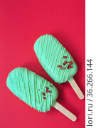 cake - popsicle in green glaze on a red background. space for text. Ice cream sweet eskimo with chocolate icing. Chocolate covered ice cream on stick. Cake sweets. Стоковое фото, фотограф Nataliia Zhekova / Фотобанк Лори