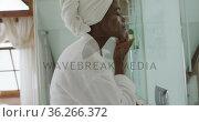 African american attractive woman applying face cream in bathroom. Стоковое видео, агентство Wavebreak Media / Фотобанк Лори