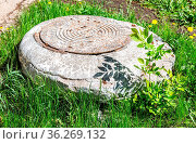 Old rusty metal manhole with cover and cement foundation on the grass... Стоковое фото, фотограф Zoonar.com/Alexander Blinov / easy Fotostock / Фотобанк Лори