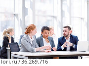 Business team sitting by the table with laptop and documents in office. Стоковое фото, фотограф Zoonar.com/Tatiana Badaeva / easy Fotostock / Фотобанк Лори