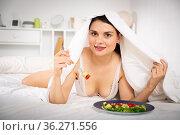 Woman in bathrobe eating vegetable salad under blanket in bed. Стоковое фото, фотограф Яков Филимонов / Фотобанк Лори