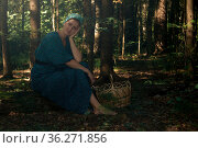 Young woman in folk peasant clothes with a basket for collecting wild plants sits on a log in the coniferous forest. Стоковое фото, фотограф Евгений Харитонов / Фотобанк Лори
