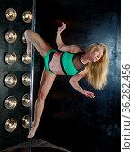Pole dance, sexy blonde girl posing while doing handstand. Стоковое фото, фотограф Zoonar.com/MYCHKO / easy Fotostock / Фотобанк Лори