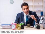 Young businessman employee eating alarm-clock. Стоковое фото, фотограф Elnur / Фотобанк Лори