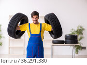 Young male garage worker with tyre at workshop. Стоковое фото, фотограф Elnur / Фотобанк Лори
