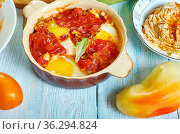 Shakshouka, dish of eggs poached in a sauce of tomatoes, olive oil... Стоковое фото, фотограф Zoonar.com/MYCHKO / easy Fotostock / Фотобанк Лори