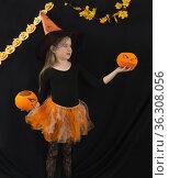 Девочка школьного возраста в костюме ведьмы с оранжевыми тыквами-конфетницами в руках на черном фоне. Стоковое фото, фотограф Наталья Гармашева / Фотобанк Лори