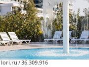 Sun loungers stand by the pool with a children's waterfall fountain. Стоковое фото, фотограф Tetiana Chugunova / Фотобанк Лори
