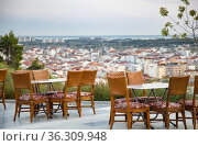 Antique chairs and tables of a street cafe overlooking the city of Manavgat, Turkey. Стоковое фото, фотограф Tetiana Chugunova / Фотобанк Лори