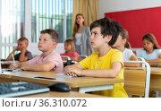 Schoolboy sitting in classroom during lesson in elementary school. Стоковое фото, фотограф Яков Филимонов / Фотобанк Лори