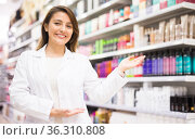 Positive salesgirl helping to choose hair products in cosmetic store. Стоковое фото, фотограф Татьяна Яцевич / Фотобанк Лори