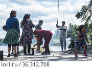 Stockholm, Sweden A family from Bangladesh picknicking on a dock ... Редакционное фото, фотограф A. Farnsworth / age Fotostock / Фотобанк Лори