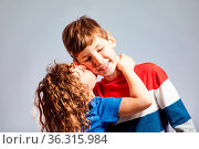 The little girl with curly hair kiss her brother. The children stand... Стоковое фото, фотограф Zoonar.com/OKSANA SHUFRYCH / easy Fotostock / Фотобанк Лори