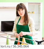 Young woman ironing clothing at home. Стоковое фото, фотограф Elnur / Фотобанк Лори