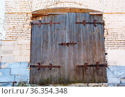 Old wooden gate with forged massive metal hinges. Стоковое фото, фотограф Zoonar.com/Alexander Blinov / easy Fotostock / Фотобанк Лори