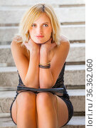 Short-haired blonde is sitting on steps with a slight smile. Стоковое фото, фотограф Emil Pozar / age Fotostock / Фотобанк Лори