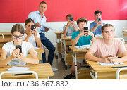 Teen pupils using mobile phones during lesson. Стоковое фото, фотограф Яков Филимонов / Фотобанк Лори