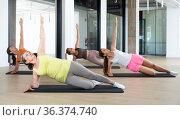 Group of women making yoga at gym. Extended triangle pose. Стоковое фото, фотограф Яков Филимонов / Фотобанк Лори