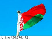 National flag of Belarus waving in the wind against the blue sky. Стоковое фото, фотограф Zoonar.com/Alexander Blinov / easy Fotostock / Фотобанк Лори