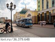 Велосипедист возле фонаря смотрит на автобус, едущий мимо здания главного железнодорожного вокзала г. Красноярск. Редакционное фото, фотограф Светлана Попова / Фотобанк Лори