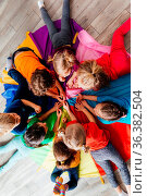 Top view preschoolers in colorful t-shirts laying on multicolor cloth... Стоковое фото, фотограф Zoonar.com/OKSANA SHUFRYCH / easy Fotostock / Фотобанк Лори