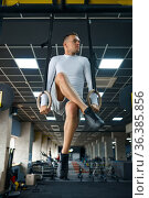 Muscular man doing endurance exercise on the rings. Стоковое фото, фотограф Tryapitsyn Sergiy / Фотобанк Лори