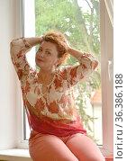 Красивая женщина сидит на подоконнике и поправляет волосы руками. Стоковое фото, фотограф Ирина Борсученко / Фотобанк Лори