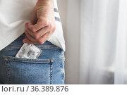 Male putting condom in jeans pocket. Prevention of sexually transmitted... Стоковое фото, фотограф Uladzislau Salikhau / easy Fotostock / Фотобанк Лори