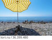 An umbrella from the sun creates shade on a pebble beach . The Black Sea coast of Crimea. Стоковое фото, фотограф Алексей Маринченко / Фотобанк Лори