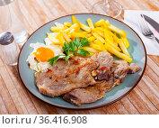 Grilled pork steak served with french fries and scrambled eggs. Стоковое фото, фотограф Яков Филимонов / Фотобанк Лори