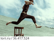 Young man in sportswear jumping over wooden chair against the background of sand dune. Стоковое фото, фотограф Евгений Ткачёв / Фотобанк Лори