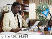 Confident african american businessman in an office talks on the phone, sitting at workdesk. Стоковое фото, фотограф Яков Филимонов / Фотобанк Лори