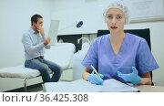 Qualified female beautician filling up client card, prescribing cosmetology procedures to young man in clinic of aesthetic medicine. Стоковое видео, видеограф Яков Филимонов / Фотобанк Лори
