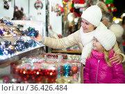 Cheerful little girl with mom choosing Christmas fairy lights at the street marke. Стоковое фото, фотограф Яков Филимонов / Фотобанк Лори