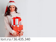 Smiling cute girl in red christmas hat holding gift boxes. Стоковое фото, фотограф Zoonar.com/Ivan Mikhaylov / easy Fotostock / Фотобанк Лори